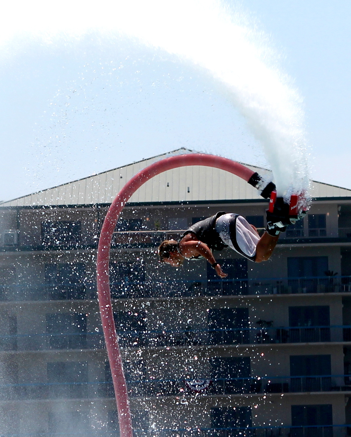 Flyboarder spinning in the air propelled by a water jetpack