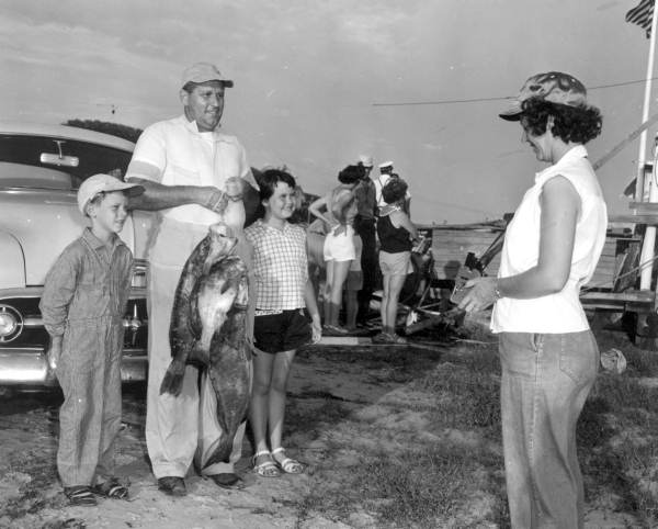 A lady takes a picture of two children and a man holding fish at the Destin Rodeo - Destin, Florida1955